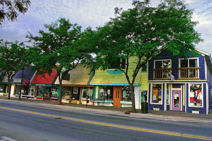The tree-shaded sidewalks of Colorful Bridge Street overlooking picturesque Round Lake.