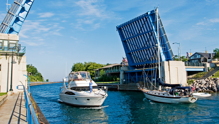 A sailboat and yacht pass under the Charlevoix drawbridge to leave and enter Charlevoix's Round Lake.