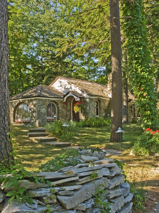 Abide cottage (1938) is nestled on a small rise under a cluster of pine trees.